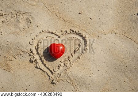 Red Heart Shape On Sandy Beach By The Ocean