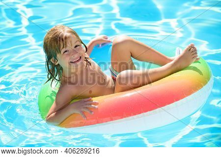 Kids Swimming With Swim Ring. Happy Kid Playing With Colorful Swim Ring In Swimming Pool On Summer D