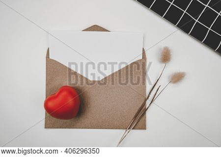 Blank White Paper Is Placed On Open Brown Paper Envelope With Red Heart, Rabbit Tail Dry Flower And