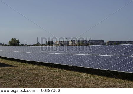 Solar Electricity Generation Concept. Solar Panels In A Field On The Outskirts Of Town. A Residentia