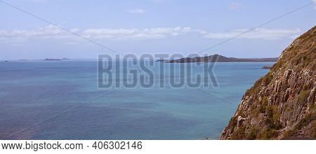 Mountains Surrounded By Water On The Shoreline And In The Distance