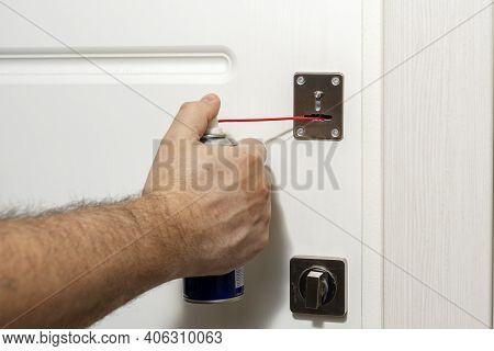 A Man Fixing A Door Lock With A Lubricant