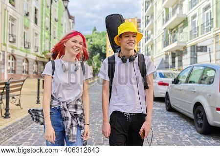 Creative Fashionable Happy Teenagers Guy And Girl Walking And Talking Along City Street With Guitar