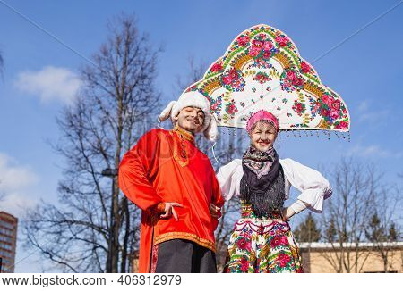 Russia Moscow 01.03.20 Jesters, Buffoons On Stilts In National Costumes. Hat With Earflaps,kokoshnik