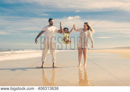 Cheerful Parents And Little Girl Enjoying Walking And Activities On Beach, Kid Holding Parents Hands