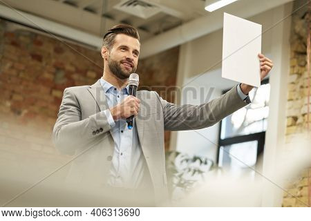 Happy Speaker Demonstrating Something On The Paper