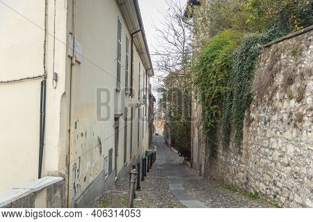 Beautiful Narrow Alley With Many Windows And Green Ivy On The Stone Wall In Brescia City. Historical