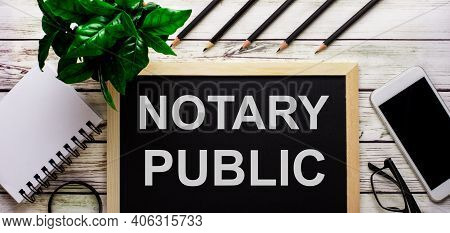 Notary Public Is Written In White On A Black Board Next To A Phone, Notepad, Glasses, Pencils And A