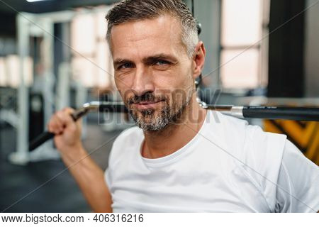 Attractive confident healthy sports man using seated lat pulldown machine in the gym, close up