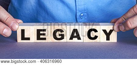 The Word Legacy Is Made Up Of Wooden Cubes By A Man. Business Concept
