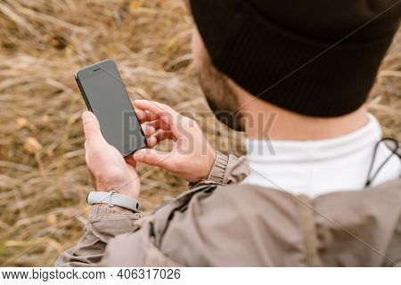 Young sportsman in hat using mobile phone while working out in nature