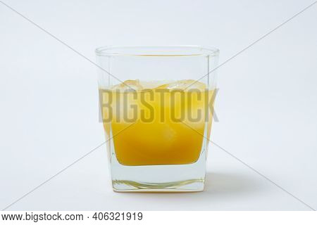 Juice With Ice In A Glass On A White Background. Natural Mango Juice. Refreshing Drink