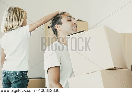 Middle-aged Dad Holding Two Carton Boxes And Sitting With Closed Eyes. Little Girl Touching Father H