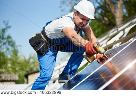 Technician Connecting Solar Photo Voltaic Panel To Metal Platform Using Screwdriver On Bright Blue S