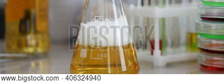 Close-up Of Yellow Alcohol Liquid In Glass Flask. Investigated Material On Working Table. Chemistry