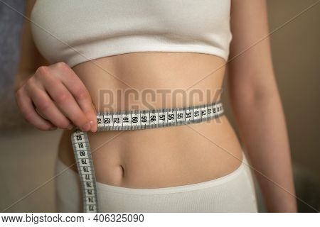 Close Up Photo Of Healthy Woman With Slim Belly Measuring Her Waists Size