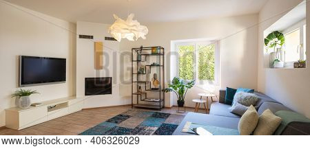 Panorama of wide modern living room with design sofa and large pillows above. Design library and small fireplace. Nobody inside