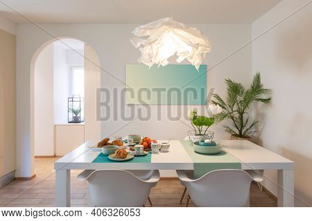 Elegant and romantic white table ready for breakfast with brioche, cups for coffee and fruits. Nobody inside