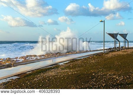 Embankment in Tel Aviv. Israel. Windy sunny day on the Mediterranean coast. Sunset. Powerful winter surf takes off with snow-white foam. Winter storm in the Mediterranean