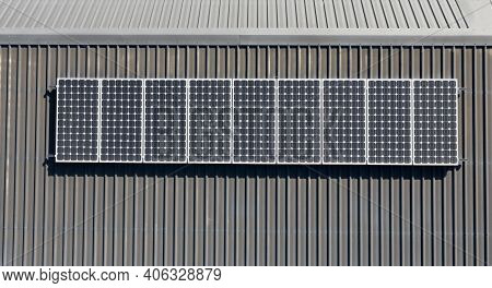 Top Down View Of Domestic Solar Panel Installation On Grey Metal Resisdential Roof