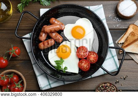 Romantic Breakfast With Fried Sausages And Heart Shaped Eggs On Wooden Table, Flat Lay. Valentine's
