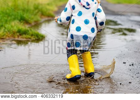 Close-up Of Little Toddler Girl Wearing Yellow Rain Boots And Walking During Sleet On Rainy Cloudy D