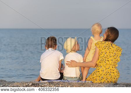 Mom And Three Children Are Resting On The Seashore. Large Family At Sea. Summer Holidays.
