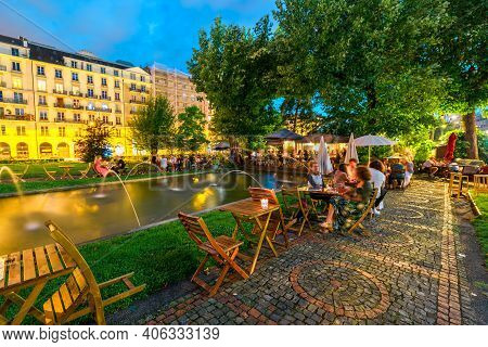 Geneva, Switzerland - Aug 14, 2020: People Drinking Outdoor Aperitif At Cottage Cafe Around The Foun