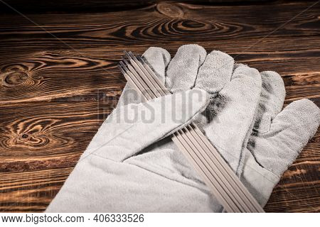 White Leather Welding Glove And Welding Electrodes On A Wooden Background. Studio Photo In Hard Ligh