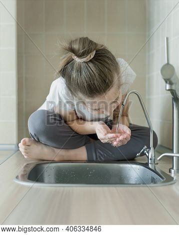 Caucasian Little Girl Drinking From Water Tap Or Faucet In Kitchen. Hands Open For Drinking Tap Wate