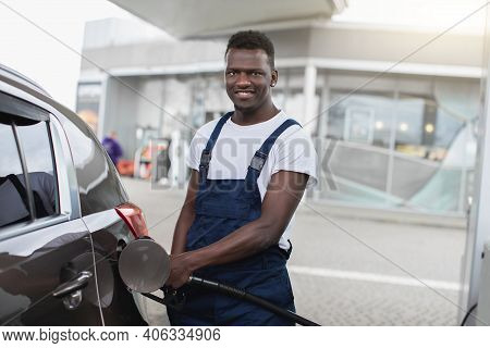 Portrait Of A Smiling African American Gas Station Worker In Workwear, Refueling Luxury Car With Gas