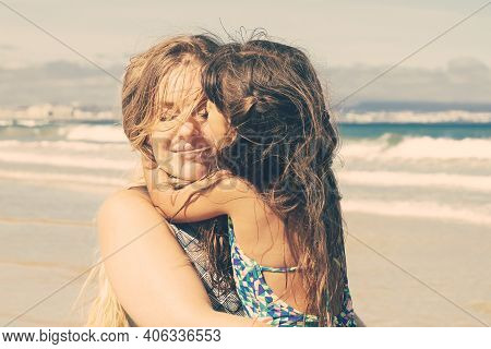 Peaceful Relaxed Young Mom Holding Little Daughter In Arms, Spending Leisure Time With Kid On Beach