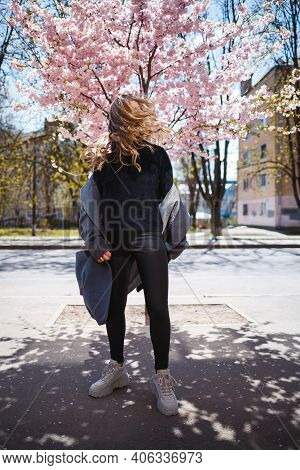 Young Slender Female Model With Long Wavy Hair And, Dressed In A Gray Coat, Sneakers, Spinning On Th