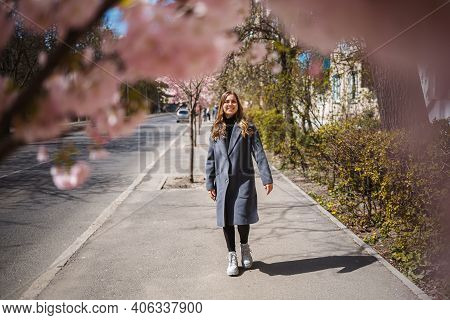 Sakura Branches With Flowers On A Tree On The City Streets. Happy Woman Girl In A Gray Palette Walks