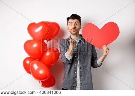Valentines Day And Love Concept. Romantic Boy Showing Heart Card And Blowing Air Kiss At Camera, Loo