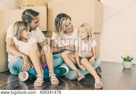 Happy Dad And Mom, Sitting On Floor, Holding Kids And Smiling. Caucasian Family With Two Daughters R