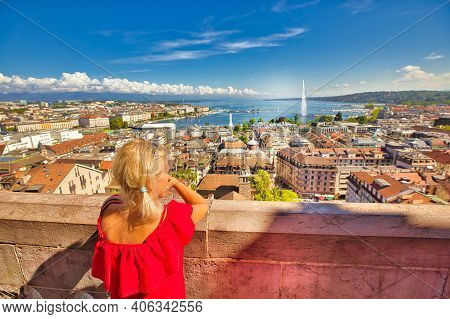 Back View Of Woman Tourist Looking Geneva Skyline, Jet Deau Fountain, Lake Leman, Bay And Harbor Fro