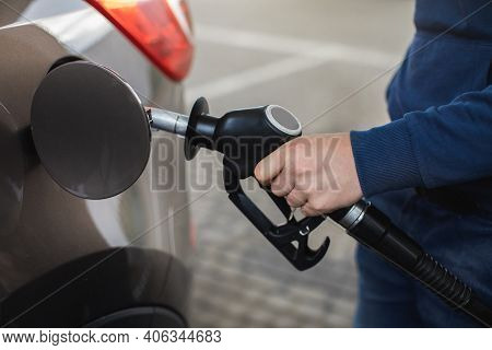 Closeup Of Mans Hands Pumping Gasoline Fuel In Car At Gas Station. Petrol Or Gasoline Being Pumped I