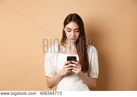 Pretty Woman Texting On Smartphone Cell Phone, Reading Screen And Smiling, Standing On Beige Backgro