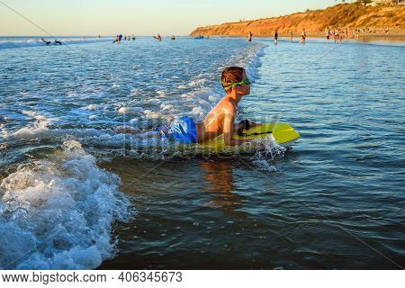 Boy Riding Bodyboard While Wearing Swimming Goggles On The Beach At Sunset In South Australia