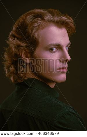 Men's beauty. Portrait of a handsome young man with wavy blond hair on a black background.