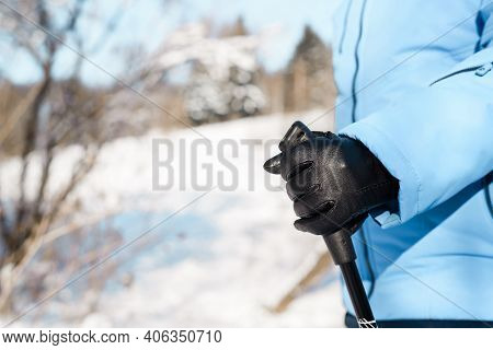 Female Hands In Gloves Holding Nordic Walking Sticks, Close-up In Profile. Active Lifestyle Concept.