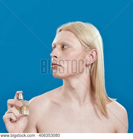 Young Caucasian Man With Long Blond Hair Spraying Perfume On Naked Neck While Standing On Blue Backg