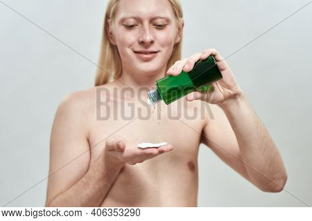 Young Caucasian Blond Man With Long Hair Applying Facial Tonic On Cotton Pad While Standing On Light