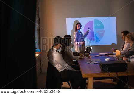 Graphs. Female Speaker Giving Presentation In Hall At University Workshop. Audience Or Conference Ha