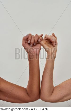 Close Up Shot Of Two Female Hands Making Pinky Swear. Promise Hand Gesture Isolated Over Light Backg