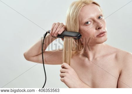 Young Caucasian Man Applying Hair Straightener On Long Blond Hair While Standing On White Background