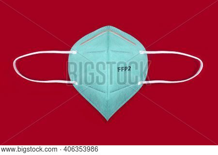 Green Ffp2 N95 Protective Face Mask On Red Background. Protection And Prevention Against Coronavirus