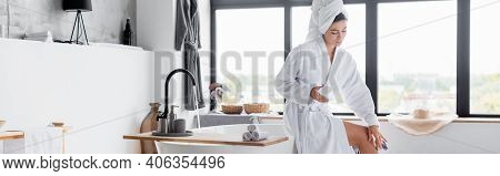 Woman In Bathrobe Applying Cosmetic Cream On Leg In Bathroom, Banner