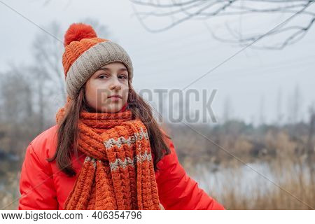 Girl In Winter Clothes. Teenager Girl In An Orange Jacket, Orange Hat And Scarf